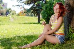 Muchacha feliz que se sienta en el árbol en parque el día de verano Foto de archivo