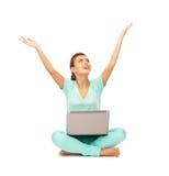 Muchacha feliz que se sienta en el piso con el ordenador portátil Imágenes de archivo libres de regalías