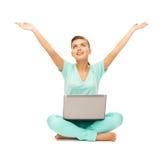 Muchacha feliz que se sienta en el piso con el ordenador portátil Fotos de archivo libres de regalías
