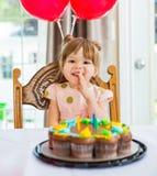 Muchacha feliz que se sienta en Front Of Birthday Cake imágenes de archivo libres de regalías