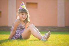 Muchacha feliz que se sienta en gras verdes en la fiesta de cumpleaños Imagenes de archivo
