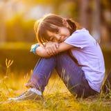 Muchacha feliz que se sienta en hierba en jardín Fotos de archivo