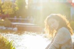 Muchacha feliz que se sienta en hierba en la puesta del sol Fotografía de archivo libre de regalías