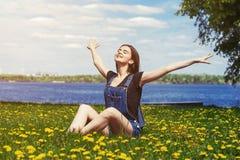 Muchacha feliz que se sienta en hierba verde Imagenes de archivo
