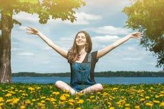 Muchacha feliz que se sienta en hierba verde Fotos de archivo libres de regalías