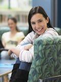 Muchacha feliz que se sienta en la butaca en biblioteca Foto de archivo libre de regalías