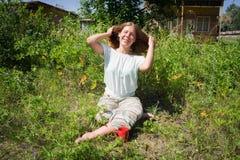 Muchacha feliz que se sienta en la hierba con una taza de café roja en el fondo de acampar, mañana del verano imagen de archivo libre de regalías
