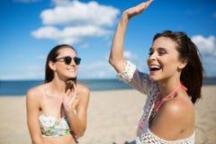 Muchacha feliz que se sienta en la playa con el amigo que aumenta la mano Foto de archivo libre de regalías