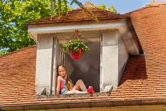 Muchacha feliz que se sienta en la repisa de la ventana del ático fotos de archivo libres de regalías