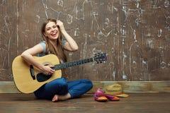 Muchacha feliz que se sienta en piso con la guitarra acústica Imagen de archivo