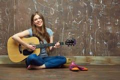 Muchacha feliz que se sienta en piso con la guitarra acústica Imágenes de archivo libres de regalías