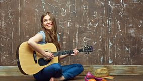 Muchacha feliz que se sienta en piso con la guitarra acústica Imagen de archivo libre de regalías