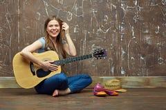 Muchacha feliz que se sienta en piso con la guitarra acústica Fotos de archivo