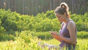 Muchacha feliz que se sienta en smartphone verde del césped y de las aplicaciones en campo escénico en el fondo de la puesta del  almacen de metraje de vídeo