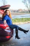Muchacha feliz que se sienta en tronco de coche Imágenes de archivo libres de regalías