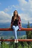 Muchacha feliz que se sienta en una cerca en un fondo de montañas Zako Foto de archivo libre de regalías