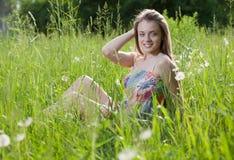 Muchacha feliz que se sienta en una hierba Foto de archivo