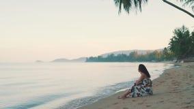 Muchacha feliz que se sienta por el océano metrajes