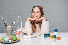 Muchacha feliz que sonríe en la cámara mientras que se sienta en la tabla con las pinturas, la cesta y los huevos de Pascua Fotos de archivo libres de regalías