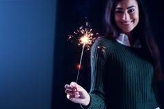 Muchacha feliz que sonríe y que sostiene un fuego artificial chispeante en su mano Foto de archivo