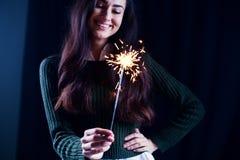 Muchacha feliz que sonríe y que sostiene un fuego artificial chispeante en su mano Imagenes de archivo