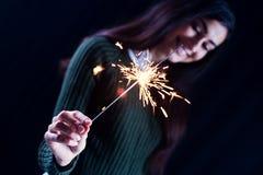 Muchacha feliz que sonríe y que sostiene un fuego artificial chispeante en su mano Fotografía de archivo libre de regalías