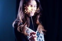 Muchacha feliz que sonríe y que sostiene un fuego artificial chispeante en su mano Foto de archivo libre de regalías