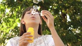 Muchacha feliz que sopla burbujas de jab?n hermosas en el parque en primavera, verano y la sonrisa C?mara lenta El viajar de la c almacen de metraje de vídeo