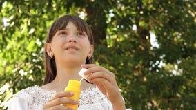 Muchacha feliz que sopla burbujas de jab?n hermosas en el parque en primavera, verano y la sonrisa C?mara lenta El viajar de la c almacen de video