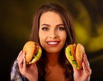 Muchacha feliz que sostiene dos pequeñas hamburguesas de la comida rápida Imagen de archivo