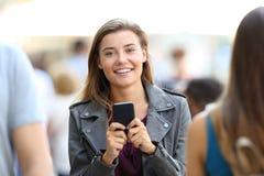 Muchacha feliz que sostiene el teléfono y que le mira Imagen de archivo libre de regalías