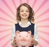 Muchacha feliz que sostiene la hucha Foto de archivo libre de regalías