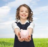 Muchacha feliz que sostiene la hucha en las palmas Fotos de archivo libres de regalías