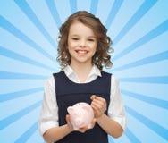 Muchacha feliz que sostiene la hucha y la moneda Imagen de archivo