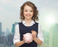 Muchacha feliz que sostiene la hucha y la moneda Imágenes de archivo libres de regalías