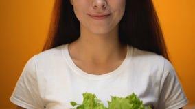 Muchacha feliz que sostiene la lechuga, productos de recomendación vegetarianos del eco, dieta sana metrajes