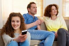 Muchacha feliz que sostiene la televisión teledirigida con los padres en fondo Fotos de archivo libres de regalías