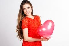 Muchacha feliz que sostiene los globos rojos del corazón Fotografía de archivo