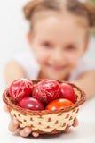 Muchacha feliz que sostiene los huevos de Pascua en una cesta Imagen de archivo libre de regalías