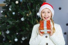 Muchacha feliz que sostiene los regalos Para la Navidad que espera Imagenes de archivo