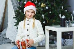Muchacha feliz que sostiene los regalos Para la Navidad que espera Foto de archivo libre de regalías