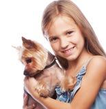 Muchacha feliz que sostiene su perro precioso del terrier de Yorkshire aislado encendido Fotos de archivo