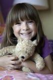 Muchacha feliz que sostiene un oso de peluche imagenes de archivo