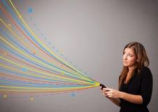 Muchacha feliz que sostiene un teléfono con las líneas abstractas coloridas Imagen de archivo libre de regalías