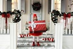 Muchacha feliz que sostiene una caja grande con un regalo concepto de la Navidad y de la gente imágenes de archivo libres de regalías