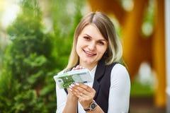 Muchacha feliz que sostiene una pila de billetes de banco euro y de sonrisa Negocio, renta, concepto del éxito foto de archivo