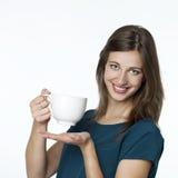 Muchacha feliz que sostiene una taza blanca grande de té Fotografía de archivo
