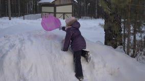 Muchacha feliz que sube en la colina de la nieve para el montar a caballo divertido Actividades felices del invierno almacen de metraje de vídeo