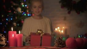 Muchacha feliz que toma la caja de regalo debajo del árbol de navidad maravillosamente adornado, día de fiesta almacen de video