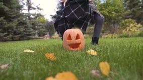 Muchacha feliz que toma la calabaza Jack en las manos, jugando en yarda, celebración de Halloween metrajes